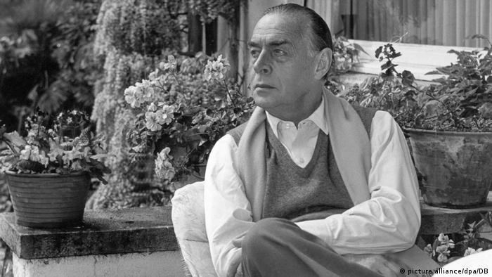 Erich Maria Remarque in seinem Haus am Lago Maggiore. Er sitzt auf einer Veranda und trägt Hemd und eine Wollweste