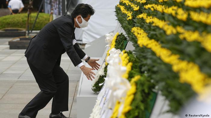 जापान के प्रधानमंत्री शिंजो आबे शांति स्मारक पर फूल चढ़ाते हुए.