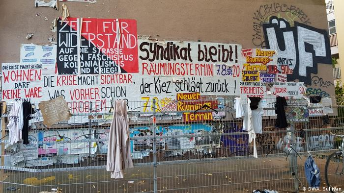 Several posters on the wall of a building showing the neighborhood's strong support for the Syndikate bar, with one poster reading Time for Resistance