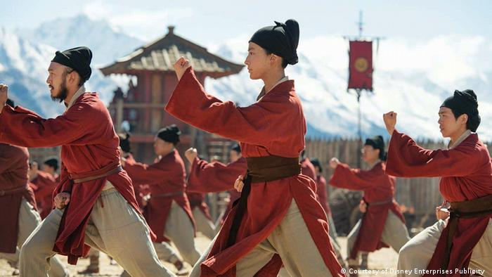 Actress Liu Yifei among other Chinese warriors in red caps and tan pants (Courtesy of Disney Enterprises Publicity )