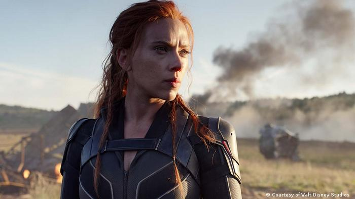 Scarlett Johansson as the superheroine the Black Widow, stands in a smoking wasteland, wearing a futuristic costume and looking pensive.