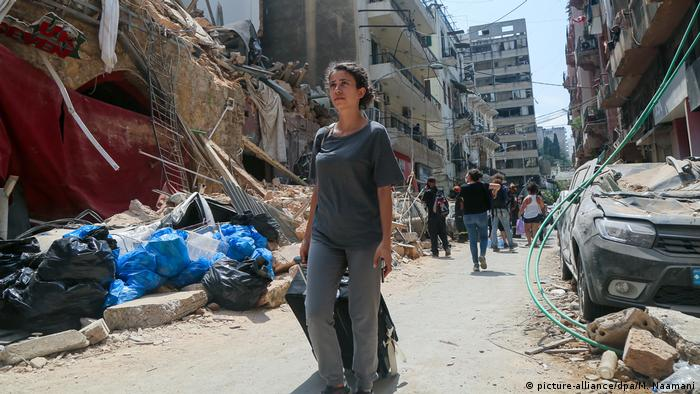 People on a rubble-filled street in Beirut