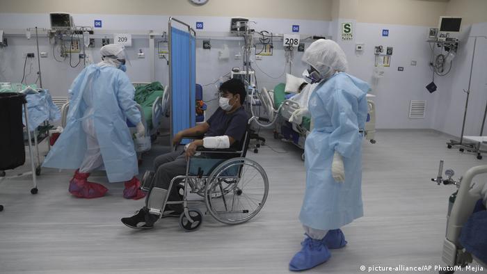 Cadeirante dentro de ambiente hospitalar com pessoas de máscara