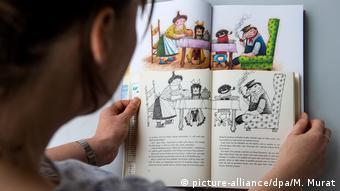 Eine Frau hält eine alte und eine neue Ausgabe des Kinderbuches Jim Knopf in den Händen. (Bild: picture-alliance/dpa/M. Murat)