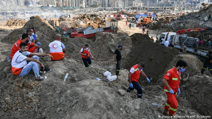 Rettungshelfer sitzen auf Trümmerbergen (picture-alliance/dpa/M. Grigoryev)