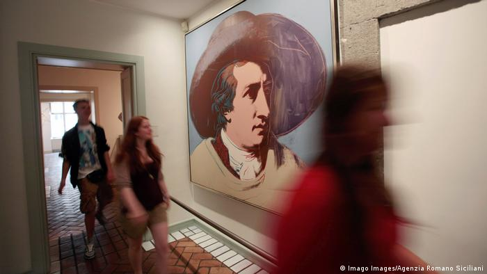 Besucher einer Ausstellung zur Deutschen Sprache und Kultur im Ausland gehen an Andy Warhols Goethe-Porträt vorbei
