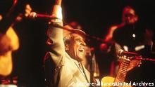 O músico Compay Segundo, um dos grandes nomes do Buena Vista Social Club, com um braço erguido e outro no violão, sorri para o público durante um concerto.