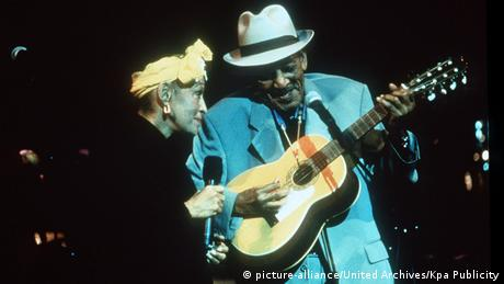 Omara Portuondo and Compay Segundo in the film, Buena Vista Social Club, man with a guitar and woman with a mike on stage