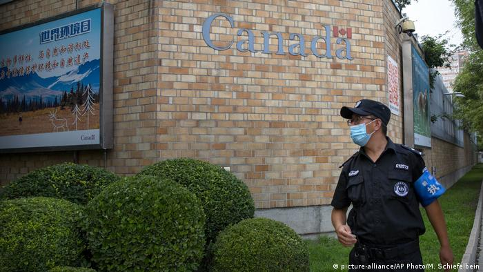 A security officer wearing a face mask to protect against the coronavirus stands outside the Canadian Embassy in Beijing,