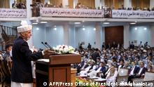 In this handout photograph taken on August 7, 2020 and released by the Press Office of President of Afghanistan, Afghan President Ashraf Ghani (L) gestures as he speaks during the first day of the Loya Jirga, a grand assembly of Afghan elders, at the Loya Jirga Hall in Kabul. - Thousands of Afghans began a three-day gathering in Kabul on August 7 to decide whether to release about 400 Taliban prisoners, including many involved in attacks that killed scores of Afghans and foreigners. (Photo by - / Press Office of President of Afghanistan / AFP) / RESTRICTED TO EDITORIAL USE - MANDATORY CREDIT AFP PHOTO / PRESS OFFICE OF PRESIDENT OF AFGHANISTAN - NO MARKETING - NO ADVERTISING CAMPAIGNS - DISTRIBUTED AS A SERVICE TO CLIENTS