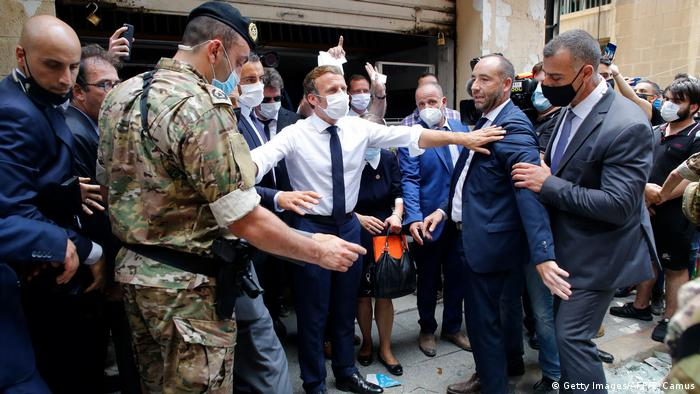 French President Emmanuel Macron gestures as he visits a devastated street of Beirut
