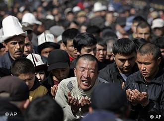 Kyrgyz pray as they gather to mourn revolt victims on central square in Bishkek, Kyrgyzstan, Friday, April 9, 2010.