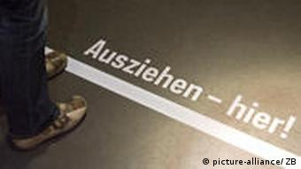 Ein Besucher steht vor der Line mit der Aufschrift Ausziehen - hier in einem Raum des ehemaligen Geschlossenen Jugendwerkhofes Torgau in der heutigen Gedenkstätte in Torgau (Foto: DPA)