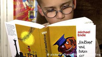 Ein Junge liest im Buch Jim Knopf und Lukas der Lokomotivführer
