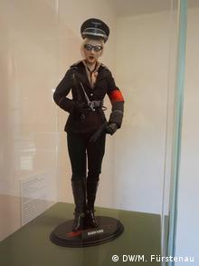 Eine weibliche Puppe in einer Vitrine mit Waffe und SS_Uniform