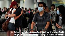 A couple (L) hugs as passengers wearing masks arrive at the Hong Kong international airport on May 2, 2009. The first confirmed case of swine flu in Asia was recorded in Hong Kong on May 1, after a Mexican man who arrived via Shanghai tested positive. AFP PHOTO/Philippe Lopez (Photo credit should read PHILIPPE LOPEZ/AFP via Getty Images)