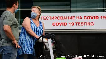 Мужчина и женщина стоят возле центра тестирования на новый корнавирус