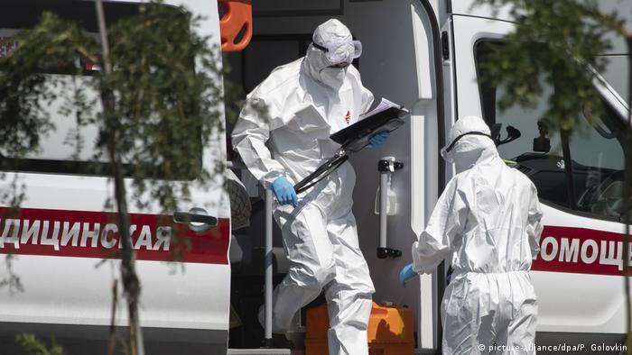 Врачи в защитных костюмах и микроавтобус скорой медицинской помощи в Коммунарке