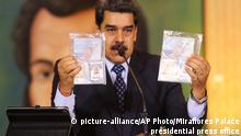 Nciolas Maduro holds up the passports of the two imprisoned men (picture-alliance/AP Photo/Miraflores Palace presidential press office)