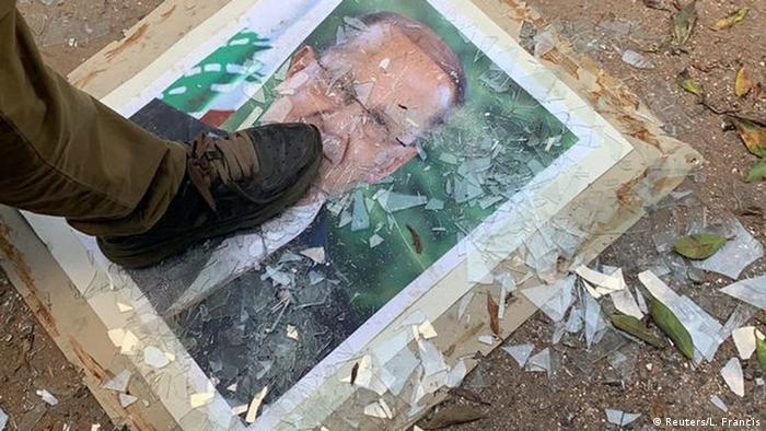 تصویر میشل عون، رئیس جمهوری لبنان، زیر پای معترضان. مخالفان میشل عون را حامی حزبالله لبنان میدانند.