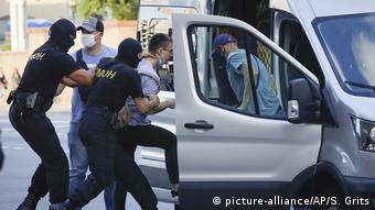 Сотрудники ОМОНа заводят задержанного в Минске мужчину в микроавтобус Ford