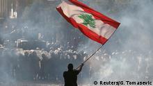BdTD | Libanon | Ein Demonstrant schwenkt die libanesische Flagge vor der Bereitschaftspolizei
