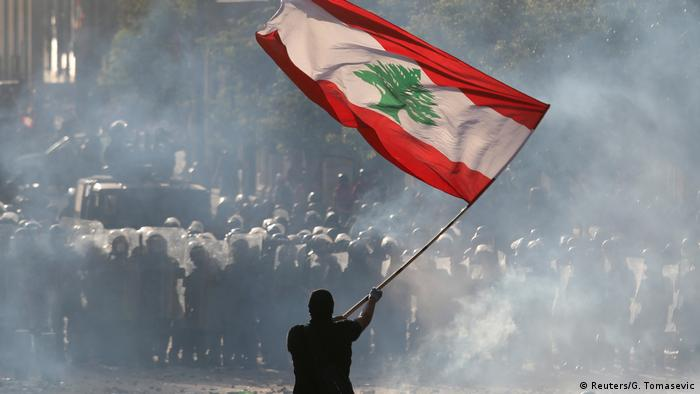 A protesters lifts the Lebanese flag in front of police (Reuters/G. Tomasevic)