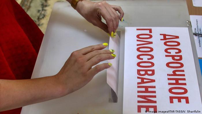 Женщина опубкает избирательный бюллетень в урну, на которой написано Досрочное голосование