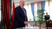 Belarusian President Alexander Lukashenko casts his ballot at a polling station during the presidential election in Minsk, Belarus, Sunday, Aug. 9, 2020. Belarusians are voting on whether to grant their authoritarian president a sixth term in office, following a campaign marked by unusually strong demonstrations by opposition supporters frustrated with the country's stumbling economy, political repression and weak response to the coronavirus pandemic. (AP Photo/Sergei Grits)