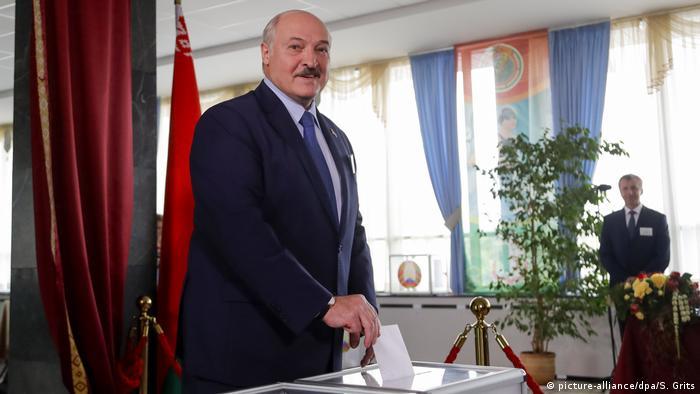 Президент Александр Лукашенко опускает избирательный бюллетень в урну для голосования.