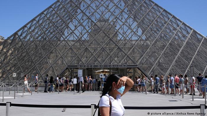 Seorang wanita mengenakan masker wajah di depan Museum Louvre (picture alliance / Xinhua News Agency)