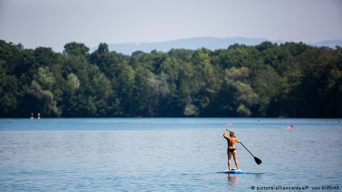 A woman paddle boards in Freiburg (picture-alliance/dpa/P. von Ditfurth)