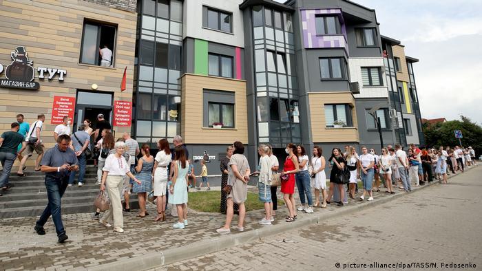 Жители деревни Боровляны под Минском стоят в очереди у входа на избирательный участок.