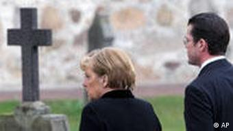 Angela Merkel and Karl-Theodor zu Guttenberg in a graveyard.