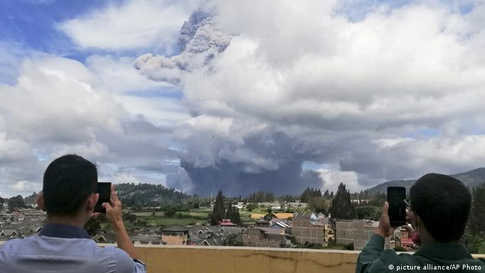Indonesian men use their mobile phones to take photos as Mount Sinabung spews volcanic materials into the air