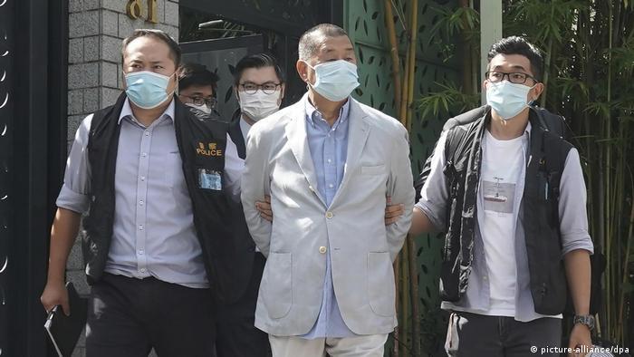 Jimmy Lai, empresário do vestuário que fundou grupo de mídia pró-democracia em Hong Kong, é levado algemado por policiais