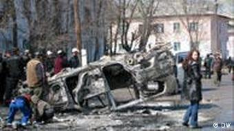 Люди смотрят на перевернутый автомобиль на улице Бишкека