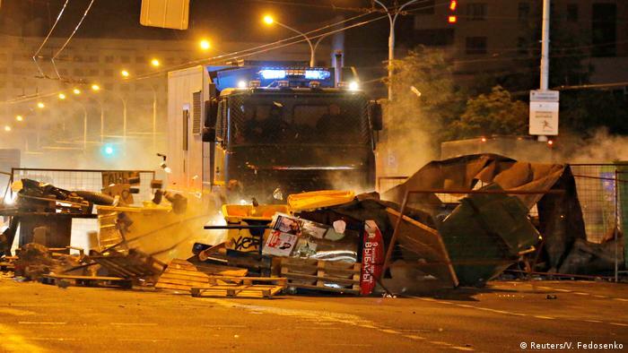 Ein Polizei-Lkw schiebt in Minsk von den Demonstranten errichtete Barrikaden zur Seite (Foto: Reuters/V. Fedosenko)