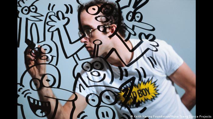 Künstler Keith Haring zeichnet Figuren auf eine Glaswand (Keith Haring Foundation)