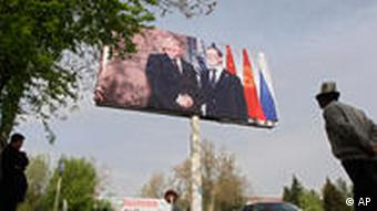 A Kyrgyz man walks under a poster with the images of Russian President Dmitry Medvedev and his Kyrgyz counterpart Kumanbek Bakyev
