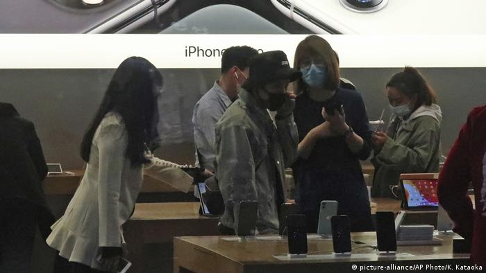 People wearing face mask go out for shopping at Apple Store of a commercial complex in Sanlitun, Beijing