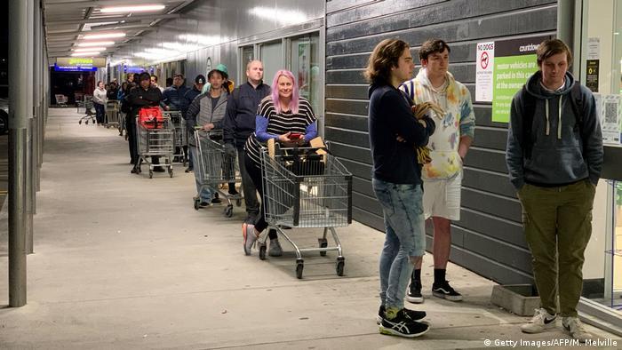 New Zealanders wait to enter a shopping market during a coronavirus lockdown in Johnsonville
