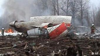 This image from Polish Television's TVP via APTN shows a firefighter walking near some of the wreckage at the crash site