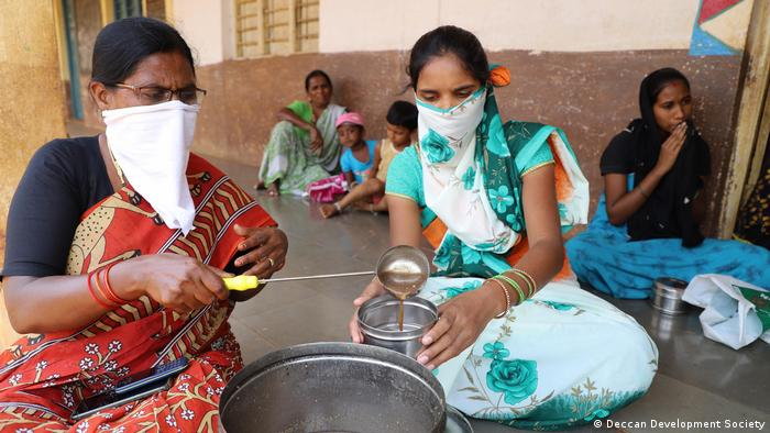 Women wearing facemasks and pouring porridge into a bowl
