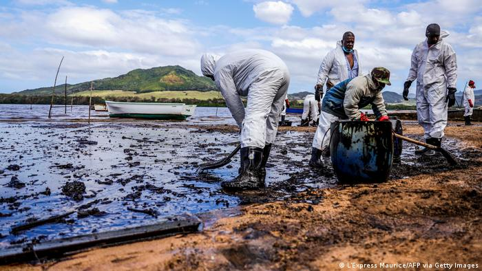 People scooping oil out of the water on the coast of Mauritius (L'Express Maurice/AFP via Getty Images)