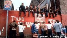 Streikposten der Gewerkschaft Solidarnosc am Eingang zur Danziger Lenin-Werft 1980. Die Streikwelle in Polen, die am 1. Juli durch eine indirekte Erhöhung der Fleischpreise begann, wurde am 31. August durch die Unterzeichnung eines Abkommens zwischen dem Streikkomitee in Stettin und der dort verhandelnden Regierungskommission beendet. Es enthält die Garantie des Streikrechts, die Gründung einer unabhängigen Gewerkschaft, soziale Verbesserungen und die Freilassung politischer Häftlinge. Auch in Danzig wurden die bereits am Vortag ausgehandelten entsprechenden Vereinbarungen an diesem Tag paraphiert. |