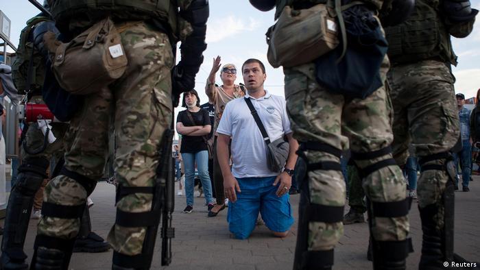 Durante protesto em Minsk, manifestante fica de joelhos na frente de policiais