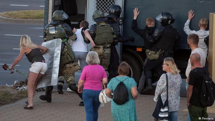 Belarusian law enforcement officers detain people near the site where a protester died on August 10 during a rally following the presidential election in Minsk (Reuters)