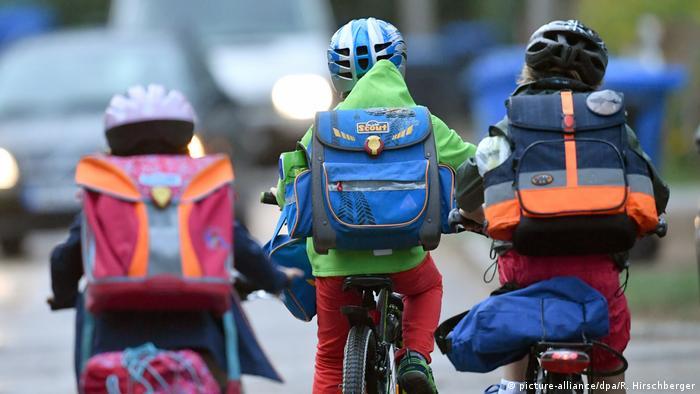 Três crianças de costas andando de bicicleta