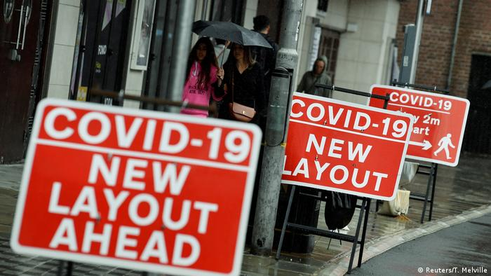 Shoppers are seen walking past social distancing signs following the outbreak of the coronavirus in London,